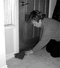 woman placing wet towel under the door